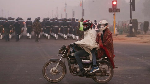 A motorcyclist and his passenger ride wearing pollution masks in New Delhi, India, on Wednesday, December 26, 2018. Authorities have ordered fire services to sprinkle water from high-rise buildings to settle dust particles. (AP Photo/Manish Swarup)