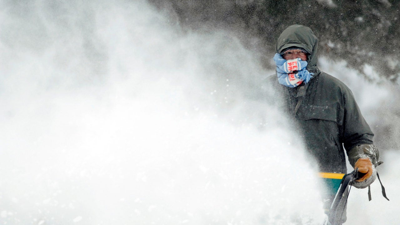 Errol Behm uses a scarf to shield his face from the blowback of snow caused by the gusty winds as he clears a sidewalk with a snowblower near Fourth Street, Thursday, Dec. 27, 2018, in Bismarck, North Dakota. (Mike McCleary/The Bismarck Tribune via AP)
