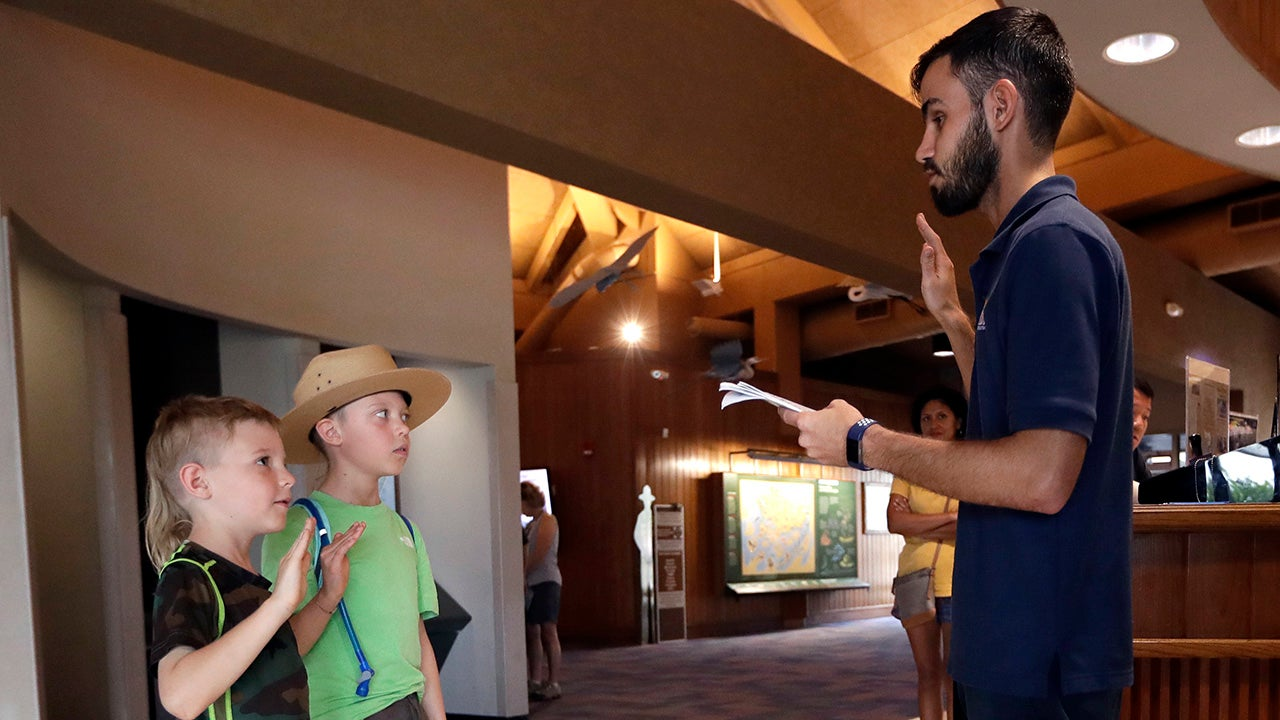 Orion and Theo Simpson are sworn in as junior rangers by Dany Garcia, right, inside the Ernest F. Coe Visitor Center in Everglades National Park on Friday, January 4, 2019, in Homestead, Florida. Garcia is being paid by the Florida National Parks Association to work in the center during the partial government shutdown.  (AP Photo/Lynne Sladky)