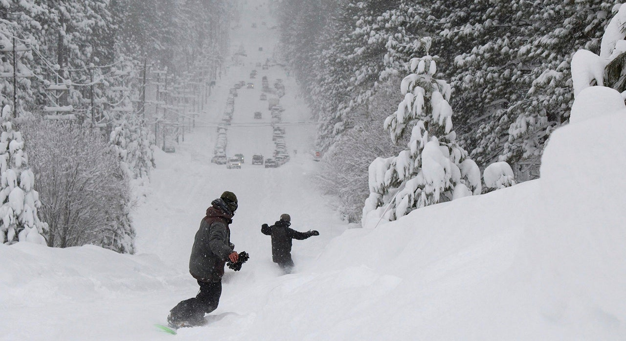 Two men snowboard down a steep street in South Lake Tahoe, California, on Friday, February 15, 2019. Skiers eager to hit the slopes had to sit out a Presidents' Day holiday weekend as heavy snow and rain fell for a fourth straight day in California's mountains, where the snow was so deep in some areas plows couldn't go out and cities were running out of places to pile it. (Ryan Hoffman/The Tahoe Tribune via AP)