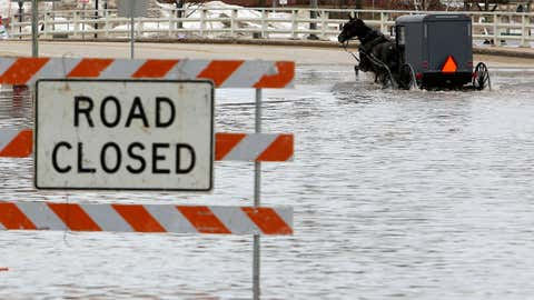 A man works his way through a flooded Galena Street as the Pecatonica River continues to rise in Darlington, Wisconsin, Thursday, March 14, 2019. (Dave Kettering/Telegraph Herald via AP)