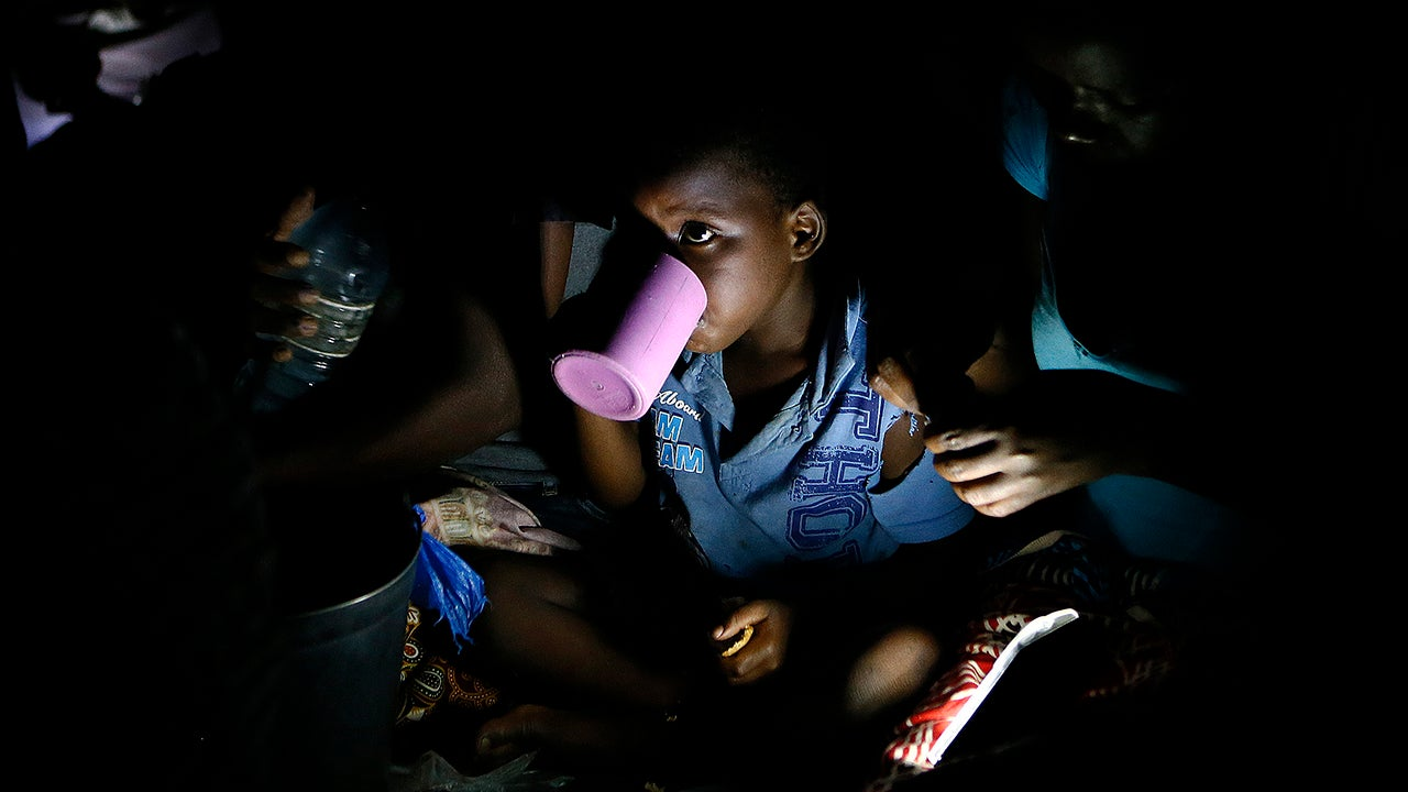 Displaced children, victims of Cyclone Idai, eat lunch at the Samora Machel Secondary School which is being used to house victims of the floods in Beira, Mozambique, Sunday, March 24, 2019. (AP Photo/Phill Magakoe)
