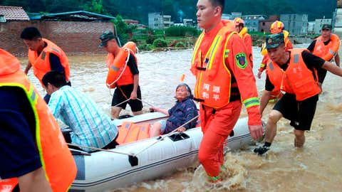 In this Monday, June 10, 2019, photo, rescuers evacuate an elderly woman on a boat in Heyuan in southern China's Guangdong province. (Chinatopix via AP)
