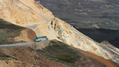 A tourist bus rides along the Denali Park Road near Polychome Pass inside Denali National Park and Preserve in Alaska. Park officials on Friday, August 16, 2019, closed the park road at Mile 30 of the 92-mile road after a culvert washout and several mudslides in the area surrounding Polychome Pass and Eielson Visitor Center created unsafe conditions. (AP Photo/Mark Thiessen)