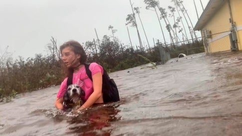 Julia Aylen wades through waist-deep water carrying her dog as she is rescued from her flooded home during Hurricane Dorian in Freeport, Bahamas, on Tuesday, September 3, 2019. (AP Photo/Tim Aylen)