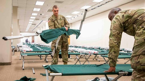 US Army National Guard Pvt. Christopher Zambuto, left, and Specialist Jermaris Hamilton assemble cots in a shelter for Hurricane Dorian evacuees inside the old Sears location at Northgate Mall, on Wednesday, Sep. 4, 2019, in Durham, NC.  (Casey Toth/The News & Observer via AP)