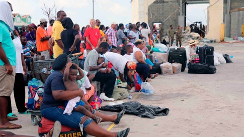 People wait in Marsh Harbour Port to be evacuated to Nassau, in Abaco, Bahamas, Friday, Sept. 6, 2019. The evacuation is slow and there is frustration for some who said they had nowhere to go after the Hurricane Dorian splintered whole neighborhoods. (AP Photo/Gonzalo Gaudenzi)