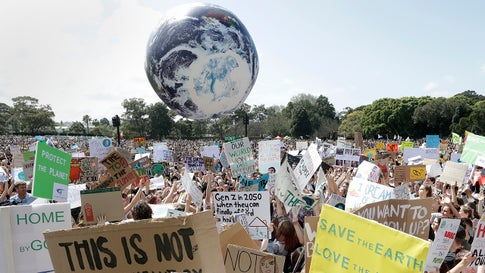 A large inflatable globe is bounced through the crowd as thousands of protestors, many of them school students, gather in Sydney, Friday, Sept. 20, 2019, calling for action to guard against climate change. (AP Photo/Rick Rycroft)