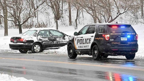 A Mankato police officer helps a motorist who slid off the road Wednesday, Nov. 27, 2019 in Mankato, Minn., after an overnight snowstorm.  A day after bringing havoc to the Rocky Mountains, a powerful winter storm rolled across the Midwest on Wednesday, threatening to scramble Thanksgiving plans for millions of people during one of the busiest travel weeks of the year.  (Pat Christman/The Free Press via AP)