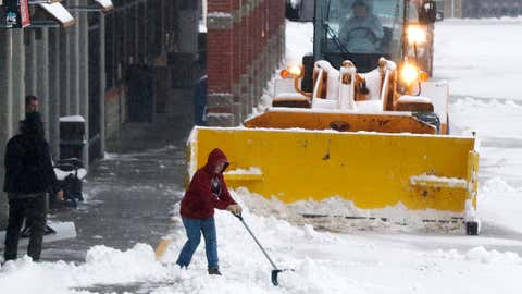 People clear snow in a shopping center on Monday, December 2, 2019, after an overnight snowfall in Marlborough, Massachusetts. (AP Photo/Bill Sikes)