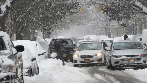 People work to shovel off their vehicles after an overnight snowfall that caused parking trouble and traffic situations on State Street, in Albany, New York, on Monday, December 2, 2019. (AP Photo/Hans Pennink)