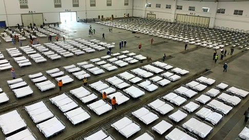 """Workers arrange beds in a convention center that has been converted into a temporary hospital in Wuhan in central China's Hubei Province, Tuesday, Feb. 4, 2020. China said Tuesday the number of infections from a new virus surpassed 20,000 as medical workers and patients arrived at a new hospital and President Xi Jinping said """"we have launched a people's war of prevention of the epidemic."""" (Chinatopix via AP)"""