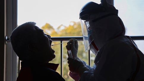 A medical worker in a protective suit collects a sample for nucleic acid tests from a suspected virus patient at a hotel being used to place people in medical isolation in Wuhan in central China's Hubei Province, Tuesday, Feb. 4, 2020. Hong Kong hospitals cut services as thousands of medical workers went on strike for a second day Tuesday to demand the border with mainland China be shut completely, as a new virus caused its first death in the semi-autonomous territory and authorities feared it was spreading locally. (Chinatopix via AP)