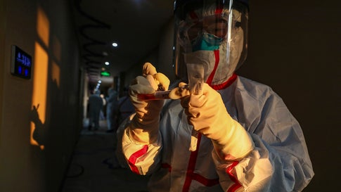 A medical worker in a protective suit writes on a tube after collecting a sample for nucleic acid tests from a suspected virus patient at a hotel being used to place people in medical isolation in Wuhan in central China's Hubei Province, Tuesday, February 4, 2020. (Chinatopix via AP)