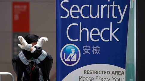A security guard gestures at the Kai Tak Cruise Terminal in Hong Kong, Wednesday, Feb. 5, 2020. A Hong Kong official says more than 1,800 people on board a cruise ship that was turned away from a Taiwanese port will be quarantined until they are checked for a new virus. (AP Photo/Vincent Yu)