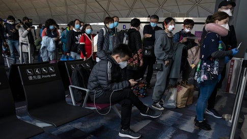 Masked passengers line up to board a flight for Beijing at the airport in Hong Kong on Sunday, Feb. 9, 2020. China's virus death toll rose above 800, passing the number of fatalities in the 2002-2003 SARS epidemic, but fewer new cases were reported in a possible sign its spread may be slowing as other nations step up efforts to block the disease (AP Photo/Ng Han Guan)