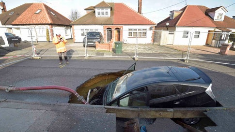 A view of a Toyota car in a sinkhole which appeared overnight in the aftermath of Storm Ciara, in Brentwood, England, Monday, Feb. 10, 2020. Storm Ciara battered the U.K. and northern Europe with hurricane-force winds and heavy rains Sunday, halting flights and trains and producing heaving seas that closed down ports. Soccer games, farmers' markets and cultural events were canceled as authorities urged millions of people to stay indoors, away from falling tree branches. (Nick Ansell/PA via AP)