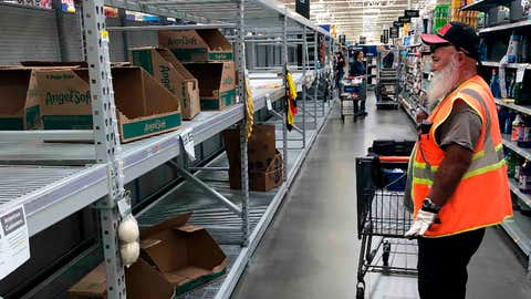 A shopper looks at a cleaned-out toilet paper aisle in a Phoenix Walmart Supercenter Friday, March 20, 2020. Arizona Gov. Doug Ducey said he's activating the National Guard to help grocery stores and food banks, halting elective surgeries and closing businesses in areas with known cases of COVID-19. (AP Photo/Bob Christie)