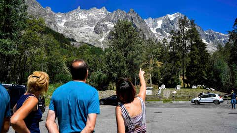 A woman points to the Planpincieux glacier, located in the Alps on the Grande Jorasses peak of the Mont Blanc massif, a popular hiking area on the south side of the Mont Blanc, near Courmayeur, northern Italy, Friday, Aug. 7, 2020. Some 70 people were evacuated Thursday in the valley below the glacier and roads closed after the threat of collapse the the fast-moving melting glacier is posing to the picturesque valley near the Alpine town of Courmayeur. (Claudio Furlan/LaPresse via AP)
