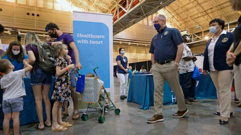 Louisiana Gov. John Bel Edwards, center, and Mayor LaToya Cantrell, second from right, pass by a family at the health station as they tour the Family Resource Center set up for Hurricane Laura evacuees at the Ernest N. Morial Convention Center in New Orleans, Friday, Sept. 4, 2020. (Max Becherer/The Times-Picayune/The New Orleans Advocate via AP)