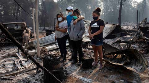 The Reyes family looks at the destruction of their home at Coleman Creek Estates mobile home park in Phoenix, Ore., Thursday, Sept. 10, 2020. The area was destroyed when a wildfire swept through on Tuesday, Sept. 8. (AP Photo/Paula Bronstein)