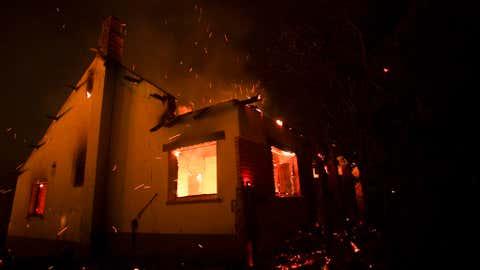 El miércoles 10 de marzo de 2021, brotaron chispas de una casa en llamas cuando estalló un incendio forestal en la región de Los Colondrinas de la provincia argentina de Subat.  (Foto AP / Matthias Carey)