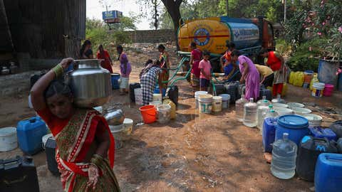 A woman walks with a vessel filled with water after collecting from a mobile water tanker at a slum area in Hyderabad, India, Saturday, March 20, 2021. World Water Day is marked annually on March 22. (AP Photo/Mahesh Kumar A.)