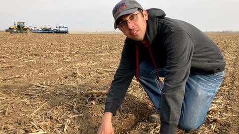 """Farmer Lance Unger describes the process of strip tillage, which disturbs the soil less than conventional tillage, in Carlisle, Indiana, on April 6, 2021. Unger is among many farmers using minimum tillage, cover cropping and other methods to improve yields while storing more carbon in the soil. """"I want to make our farm better for the fourth generation,"""" he says. (AP Photo/John Flesher)"""