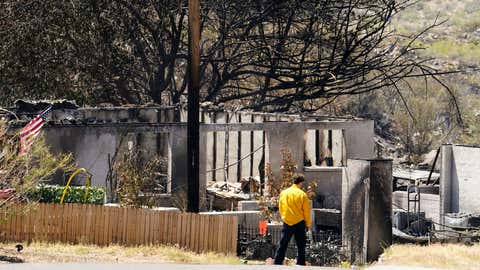 A person surveys the remains of a charred home from the Spur Fire that burned 150 acres and destroyed several homes and other structures Friday, May 28, 2021 in Bagdad, Ariz. (Rob Schumacher/The Arizona Republic via AP, Pool)