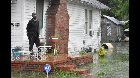 Dennis Munford watches the rising flood waters from two days of rain, flood his yard near downtown Greenwood, Miss., Thursday, June 10, 2021. Several streets were flooded, forcing residents to take to foot rather than risk flooding their vehicles if they drove them through the waters. (Tim Kalich/The Greenwood Commonwealth via AP)