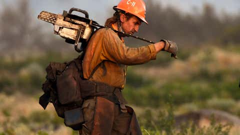 A member of the U.S. Forest Service's Trinity Hotshots firefighting crew carries a chain saw while hiking out of the burn zone Monday, June 28, 2021, at the Lava Fire north of Weed, Calif. (Scott Stoddard/Grants Pass Daily Courier via AP)