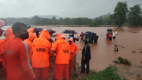 This photograph provided by India's National Disaster Response Force (NDRF) shows NDRF personnel rescuing people stranded in floodwaters in Chiplun, in the western Indian state of Maharashtra, Friday, July 23, 2021. Landslides triggered by heavy monsoon rains hit parts of western India, killing at least five people and leading to the overnight rescue of more than 1,000 other people trapped by floodwaters, an official said Friday. (National Disaster Response Force via AP)