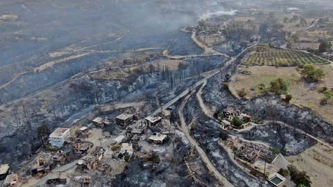 An aerial photo shows houses destroyed in a village as the fire continues to ravage forests near the Mediterranean coastal city of Manavgat, Antalya, Turkey, on Thursday, July 29, 2021. Authorities evacuated homes in southern Turkey while a blaze ignited by strong winds a forest area near the Mediterranean coastal town of Manavgat.  District Governor Mustafa Yigit said residents of the four neighborhoods were displaced by the road of fires as firefighters worked to control the blaze that broke out Wednesday.  It was not immediately clear what caused the fire but authorities said the nearby resorts were not affected.  (Suat Metin / IHA through AP)