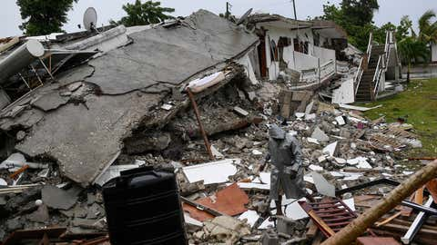 A man walks on the rubble of a collapsed hotel the morning after Tropical Storm Grace swept over Port Salut, Haiti, Tuesday, Aug. 17, 2021, three days after a 7.2 magnitude quake. (AP Photo/Matias Delacroix)
