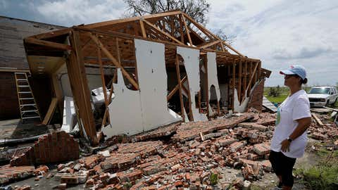 In the aftermath of Hurricane Ida, Patricia Rodrigue looks over the damage to her house Tuesday, Aug. 31, 2021, in Houma, La. (AP Photo/David J. Phillip)