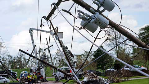 Crews begin work on downed power lines leading to a fire station, Tuesday, Aug. 31, 2021, in Waggaman, La., as residents try to recover from the effects of Hurricane Ida. (AP Photo/Steve Helber)