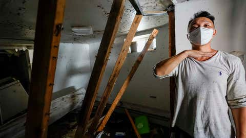 Danny Hong shows where the water reached up to him as he shows the damage in his basement apartment on 153rd St. in the Flushing neighborhood of the Queens borough of New York, Thursday, Sept. 2, 2021, in New York. The remnants of Hurricane Ida dumped historic rain over New York City, with at least nine deaths linked to flooding in the region as basement apartments suddenly filled with water and freeways and boulevards turned into rivers, submerging cars.(AP Photo/Mary Altaffer)