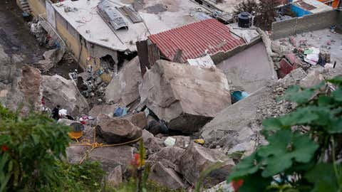 Boulders that plunged from a mountainside rests among homes in Tlalnepantla, on the outskirts of Mexico City, when a mountain gave way on Friday, Sept. 10, 2021.  A section of mountain on the outskirts of Mexico City gave way Friday, plunging rocks the size of small homes onto a densely populated neighborhood and leaving at least one person dead and 10 others missing. (AP Photo/Eduardo Verdugo)