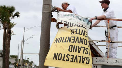 Workers remove banners from a post in front of Landry's Seafood House in Galveston, Texas, Monday, Sept. 13, 2021, as residents and business prepare for Tropical Storm Nicholas. (Jennifer Reynolds/The Galveston County Daily News via AP)