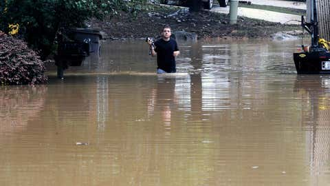 Michael Halbert wades through his flooded neighborhood in Pelham, Ala., on Thursday, Oct. 7, 2021. Parts of Alabama remain under a flash flood watch after a day of high water across the state, with as much as 6 inches of rain covering roads and trapping people. (AP Photo/Jay Reeves)