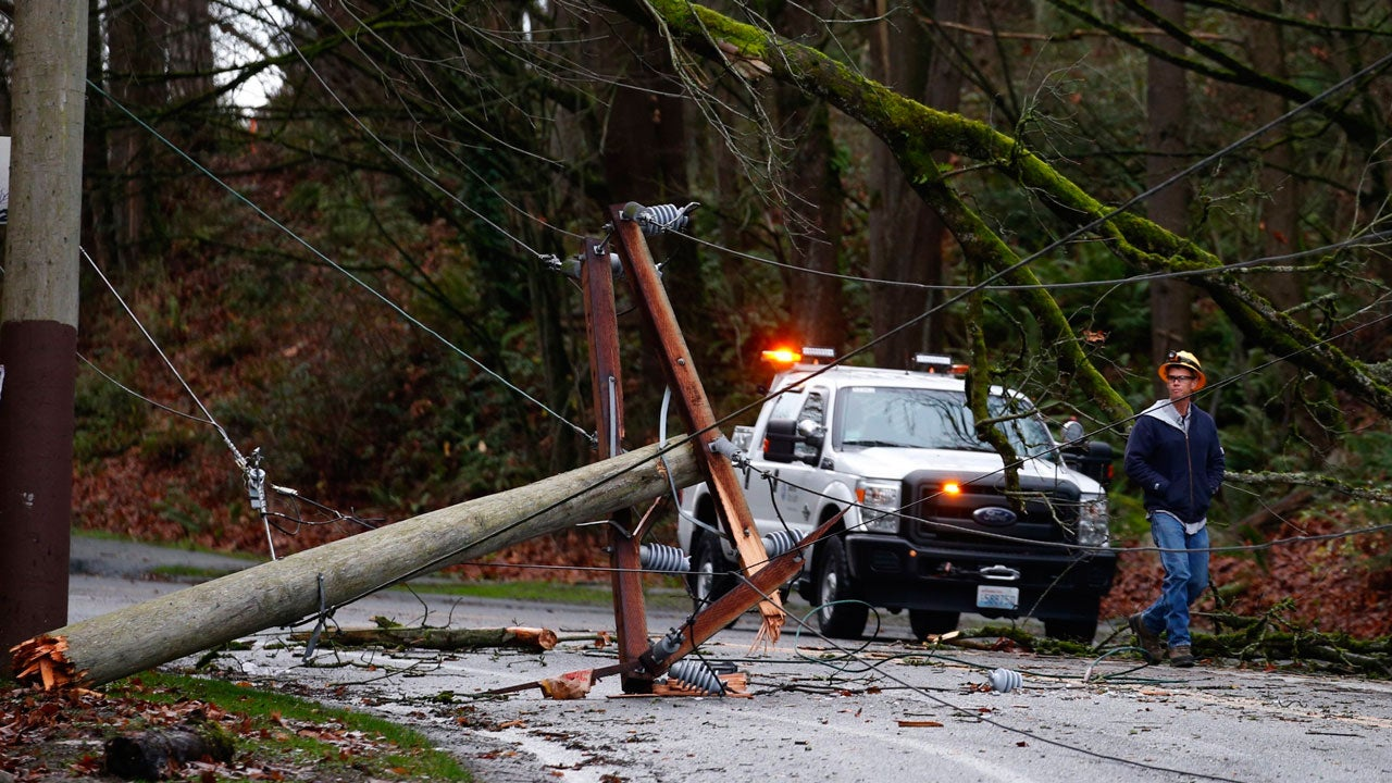 A worker from Seattle City Light checks out a snapped electric power pole and downed tree closing South Alaska Street between South Columbian Way and Beacon Avenue South between the Beacon Hill and Columbia City neighborhoods of Seattle Thursday, Dec. 20, 2018. (Bettina Hansen/The Seattle Times via AP)