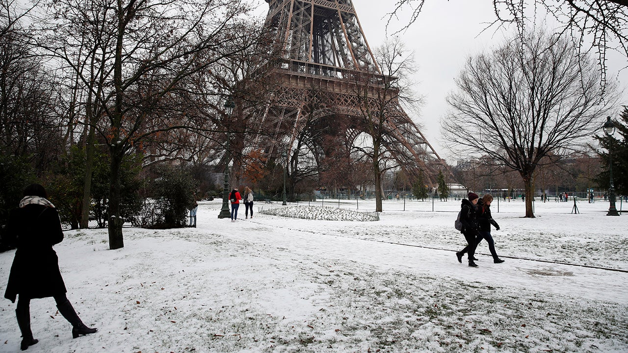 People walk past the Eiffel Tower shut down as a precautionary measure, in Paris, Tuesday, Jan. 22, 2019. France's national weather agency Meteo France says a large part of the country is on alert for dangerous levels of snow and ice and urged people to limit their movement. (AP Photo/Christophe Ena)