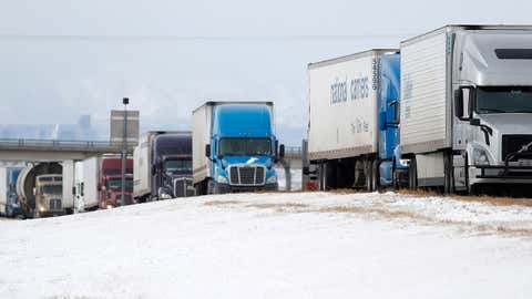 Tractor-trailers are stacked up along the shoulder of eastbound Interstate 70 near the Airpark road exit Tuesday, Jan. 22, 2019, in Aurora, Colo. Winter Storm Indra is packing high winds, which has forced the closure of the interstate east from Denver to the state's border with Kansas because of drifting snow and left travelers stranded along the corridor. (AP Photo/David Zalubowski)