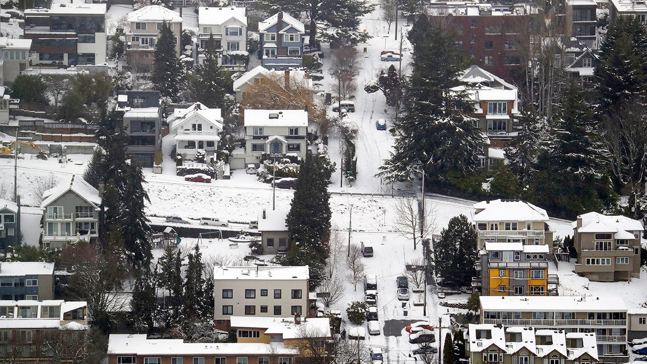 Streets, homes and cars remain snow-covered on one of Seattle's steeper hills, Queen Anne, Monday, Feb. 11, 2019. Schools and universities closed across Washington state and the Legislature cancelled all hearings as the Northwest dealt with snow and ice and prepared for more as a series of winter storms socked the region. (AP Photo/Elaine Thompson)