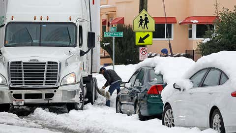 The driver of a tractor-trailer that got stuck in deep, melting snow in a residential neighborhood in Seattle tries to dig it out with a shovel borrowed from a resident of the street on Tuesday, February 12, 2019, in Seattle. After several minutes of work, he was able to move it forward and continued on. (AP Photo/Elaine Thompson)