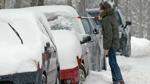 A motorist brushes show off a vehicle after Winter Storm Petra dumped seven inches, according to the National Weather Service, Wednesday, Feb. 20, 2019, in Minneapolis, setting a record for February snowfall at 30-inches. (AP Photo/Jim Mone)