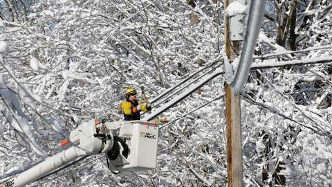 A lineman with Sussex Rural Electric Cooperative works to restore power in Vernon Township, N.J., Tuesday, Dec. 3, 2019. The last of the snow is falling over parts of New Jersey after leaving behind power outages in the northwest part of the state. (AP Photo/Seth Wenig)