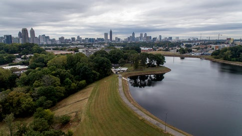 Reservoir No. 1, a 180-million-gallon water supply that has been out of service much of the past few decades, sits against the backdrop of the Atlanta skyline, on October 15, 2019. The city made repairs and brought it back online in 2017, only to shut it down again after water leaks were noticed near businesses beneath the dam. Were the dam to catastrophically fail, the water could inundate more than 1,000 single-family homes, dozens of businesses, a railroad and a portion of Interstate 75, according to an emergency action plan. (AP Photo/David Goldman)