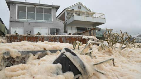 Seafoam brought by waves approaches beachfront houses after heavy rain and storms at Collaroy in Sydney's Northern Beaches on Monday, February 10, 2020. (Joel Carrett, AAP Image via AP)