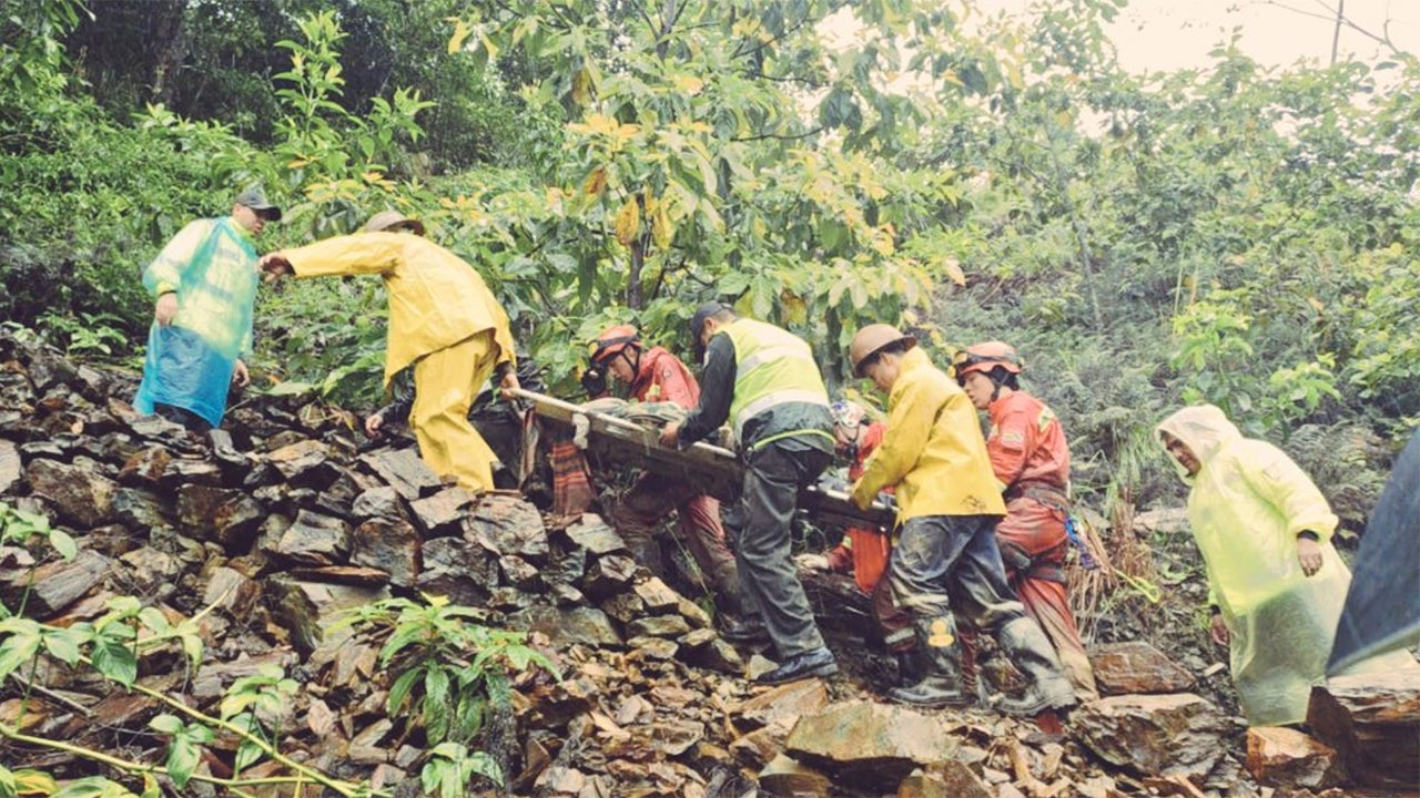 Bolivian police and rescue personnel move one of the people injured on Saturday, February 2, 2019, when a mudslide slammed into at least six cars on a highway between Caranavi and La Paz. (Bolivian Police)